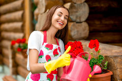 Woman watering flowers near the wooden cottage Stock Photos