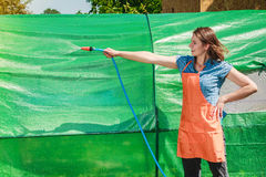 Woman watering the garden with hose Stock Photo