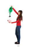 Woman watering piggybank. Royalty Free Stock Images