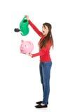 Woman watering piggybank. Stock Image