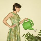 Woman watering plant. Royalty Free Stock Photo