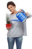 Woman watering plant in pot Stock Images