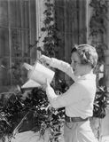 Woman watering plants in window boxes Stock Images