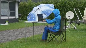 A woman in waterproof clothing works at computer under umbrella stock video