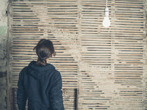 Woman by wattle and daub wall. A young woman is standing under a light bulb by an old wattle and daub wall Royalty Free Stock Image