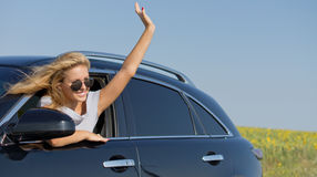 Woman waving from car window Stock Image