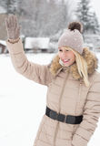 Woman waving a greeting in winter park Royalty Free Stock Photography