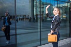 Woman waving hand in city center Stock Photos