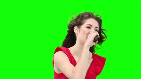 Woman waving her arms while singing into a microphone Royalty Free Stock Photos