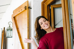 Woman waving from home window Royalty Free Stock Photo
