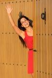 Woman waving at house entrance Royalty Free Stock Photography