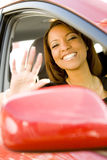 Woman waving out of car window royalty free stock image