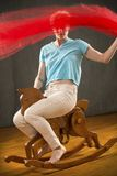 Woman waving red fabric while riding a wooden rocking horse. Young woman with short blonde hair in white pants and blue shirt waving red fabric while riding a royalty free stock images