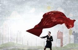 Woman waving red flag . Mixed media Royalty Free Stock Image