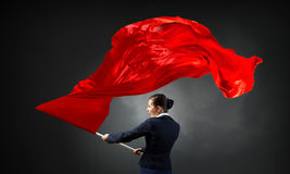 Woman waving red flag . Mixed media Stock Photos