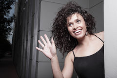 Woman waving with a smile Stock Image