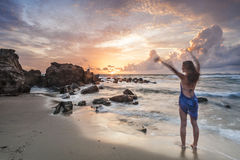 Woman waving at the sun near the sea Stock Image