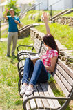 Woman waving to man sitting on bench Royalty Free Stock Image