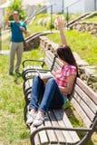 Woman waving to man sitting on bench royalty free stock image