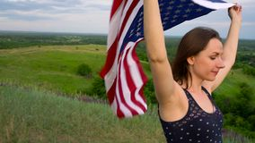 Woman waving a US flag is standing on top of a hill - the concept of Independence Day USA stock video