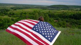 Woman waving a US flag is standing on top of a hill - the concept of Independence Day USA stock footage