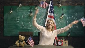 Woman waving US flags. School background. Happy patriotic woman holding USA flag while siting isolated over green board stock video footage
