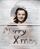 Woman waving at window with Christmas greeting Stock Photo
