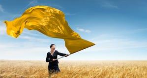 Woman waving yellow flag . Mixed media Stock Images