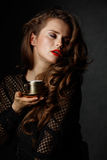 Woman with wavy brown hair and red lips enjoying cup of coffee Royalty Free Stock Photography