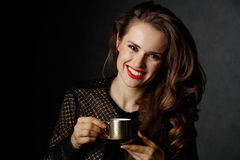 Woman with wavy brown hair and red lips holding cup of coffee Stock Photo