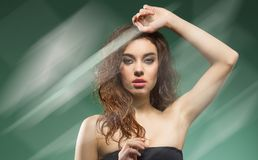 Woman with wavy hair on shoulder on green stock photos