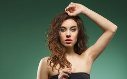 Woman with wavy hair on shoulder on green stock photo