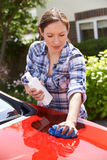 Woman Waxing Car Outside House Royalty Free Stock Images