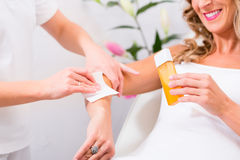 Woman at waxing hair removal in beauty parlor Royalty Free Stock Photo