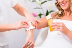 Woman at waxing hair removal in beauty parlor. Woman receiving waxing for hair removal in beauty parlor Royalty Free Stock Photo