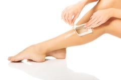 Woman waxing her leg Stock Image