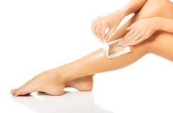 Woman waxing her leg Stock Photos