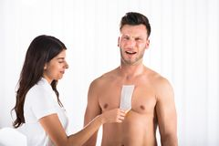 Woman Waxing Man`s Chest With Wax Strip. Close-up Of A Woman Waxing Man`s Chest With Wax Strip royalty free stock photography