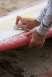 Woman waxing surfboard. A woman applies wax to her longboard surf board before a wave riding session Royalty Free Stock Photography