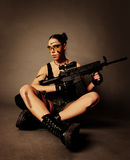 Woman with weapon. Sexy army woman posing with weapon, on gray background Stock Photo