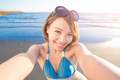 Woman wear bikini. Beauty woman wear bikini and selfie happily with sea Stock Photography