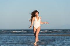 Woman wear bikini run on sea water Stock Photos