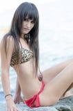 Woman wear bikini sitting on sea rocks Stock Photography