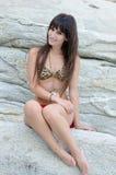 Woman wear bikini sitting on sea rocks Stock Images