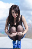 Woman wear a blue skirt and black stockings pose on the open road Royalty Free Stock Image