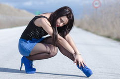 Woman wear a blue skirt and black stockings pose on the open road Stock Photography