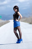 Woman wear a blue skirt and black stockings pose on the open road Stock Photo