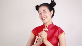 Woman wear cheongsam with gesture of congratulation in concept of happy chinese new year. Woman wear red cheongsam with gesture of congratulation in concept of stock footage