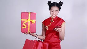 Woman wear cheongsam and using mobile phone with shopping bag and gift stock video
