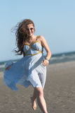 Woman wear dress running on the beach Royalty Free Stock Images